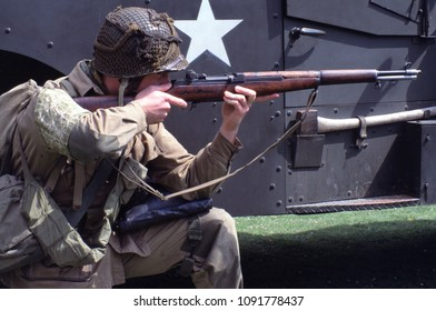Audley End House Essex UK 1996. A unidentified reenactor of WW2 kneels to fire his Garand rifle wearing the period uniform of a US Paratrooper at a reenactment of the Battle of Caen 1944.