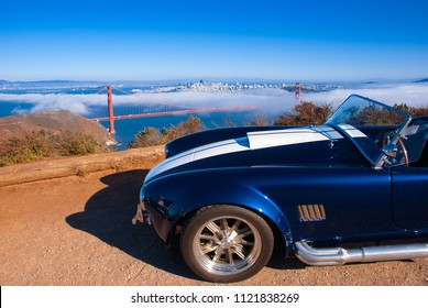 Aug 20, 2008 San Francisco, USA -Vingtage classic sport car with San Francisco Golden Gate bridge on foggy background high angle view from Marin Headland