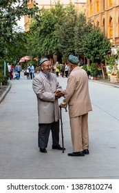 Aug 2017, Kashgar, Xinjiang, China: two local uighur men warmly shaking hands in the streets of Kashgar Old Town, a major tourist spot along the Silk Road and one of the westernmost cities of China