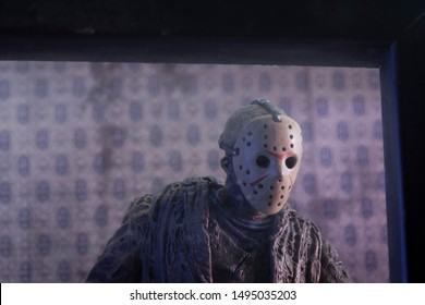AUG 31 2019: Horror film Friday the 13th killer Jason Voorhees lurking from behind a window at Camp Crystal Lake - Neca Ultimate Jason action figure