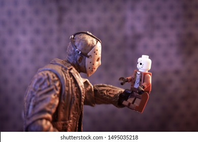 AUG 31 2019: Horror film Friday the 13th killer Jason Voorhees looking at a Lego style mini figure of himself at Camp Crystal Lake - Neca Ultimate Jason action figure / Lego style minifig