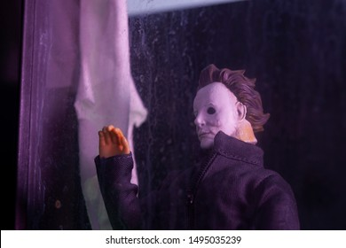 AUG 31 2019: recreation of a scene from a Halloween movie with killer Michael Myers stalking from behind a window at night - Custom action figure using Funko Savage head and Mego body