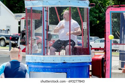 Aug 5 2017 Michigan USA; a man heckles a young boy as he throws a ball at a target to dunk the person inside. All good, wet fun during the Thrill on the hill event in Buchanan MI