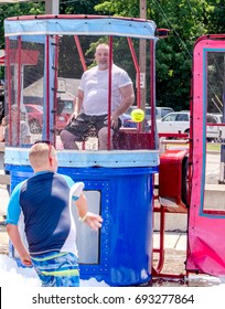 Aug 5, 2017 Michigan USA; a man in a dunk tank watches a boy throw a ball in mid flight. Wet fun on a hot summers day at the Thrill on the hill event in Buchanan Michigan