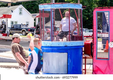 Aug 5, 2017 Michigan USA; a boy prepares to throw a ball, attempting to dunk a man in this wet dunk tank at the fun thrill on the hill event in Buchanan Michigan