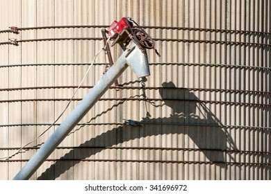 An auger attached to a concrete silo on a farm creates a wonderful shadow of its mechanical structure.