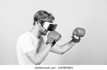Augmented 3D world. Man boxer virtual reality headset simulation. Man play game in VR glasses. Cyber sport concept. Cyber coach online training. Explore cyber space. Cyber sportsman boxing gloves.