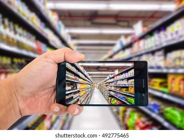 Augmented reality application for retail business concept. Hand holding smart phone with A/R application on screen to scanning products in supermarket. Represent A/R application in real business.