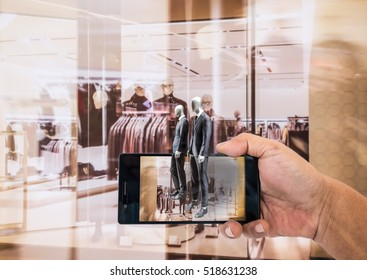 Augmented reality application for retail business concept. Hand holding smart phone with A/R application on screen to finding interested product in the store.
