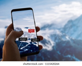 Augmented reality (AR) concept. Hand holding a smartphone and use AR application to check relevant information about the ski area in the Alps. Background is out of focus.