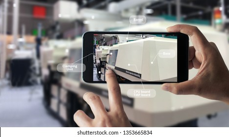 Augmented reality concept. AR. Industrial 4.0, Hand of engineer holding mobile smart phone using virtual AR to check the work of electric machine on smart factory background.
