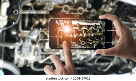 Augmented reality concept. AR. Industrial 4.0 , Hand of engineer holding mobile smart phone using virtual AR to check the work of electric machine on smart factory background.