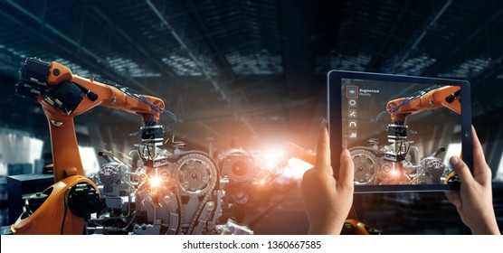 Augmented reality industrial concept. Tablet use AR application to check and control robotics automatic arms machine in factory automotive industrial with monitoring system software. Industry 4.0