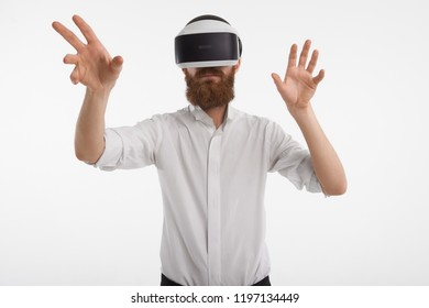Augmented reality, innovations, programming and future concept. Unshaven male with stubble posing in studio wearing rift oculus 3d headset holding hands in front of him as of touching something