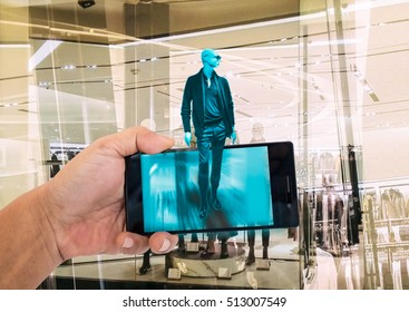 Augmented reality marketing concept. Hand holding smart phone to use A/R application to find product details in retail store.