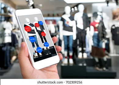 Augmented reality marketing concept. Hand holding smart phone use AR application to check number of social media like and sale price in retail fashion shop