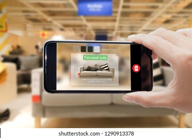 augmented reality for smart Business concept.Man hands holding mobile phone on blurred furniture shop as background