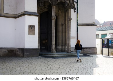 Augsburg, Germany - April 1, 2019: Woman walking across the churchyard towards the entrance of the Basilica St. Ulrich and Afra in Augsburg's city center