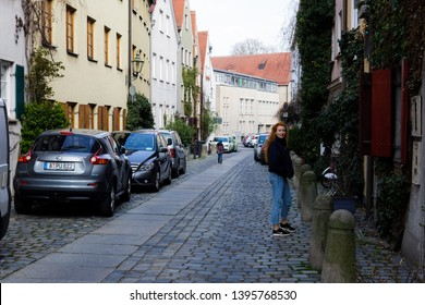 Augsburg, Germany - April 1, 2019: Woman standing in narrow alley in Augsburg's old town