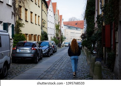 Augsburg, Germany - April 1, 2019: Woman walking through small alley in Augsburg's old town