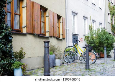 Augsburg, Germany - April 1, 2019: Bicycles and green plants in front of old buildings in Augsburg's old town