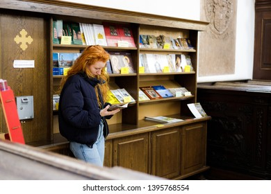 Augsburg, Germany - April 1, 2019: Woman reading a flyer in the Basilica of St. Ulrich and Afra in Augsburg's city center
