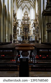 Augsburg, Germany - April 1, 2019: Lit candles and font in the Basilica St. Ulrich and Afra in Augsburg's city center