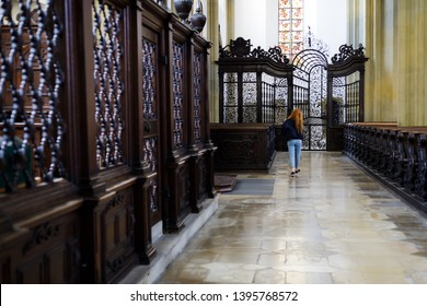 Augsburg, Germany - April 1, 2019: Woman walking alongside church pews and small chapels inside the Basilica St. Ulrich and Afra in Augsburg's city center
