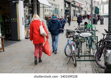 Augsburg, Germany - April 12, 2019: Woman dressed only in red carrying a red plastic bag walking along Maximilianstraße (Maximilian Street) in Augsburg's city center