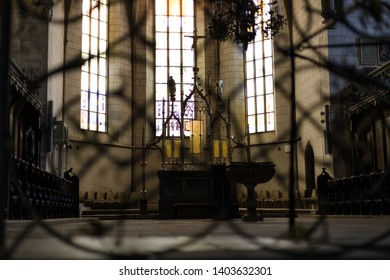 Augsburg, Germany - April 12, 2019: View of an altar with a crucifix and a font through a metal fence inside of the Augsburger Dom (Translation: Cathedral of Augsburg)