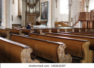 Augsburg, Germany - April 12, 2019: Man sitting on wooden church pew in the Augsburger Dom (Translation: Cathedral of Augsburg)
