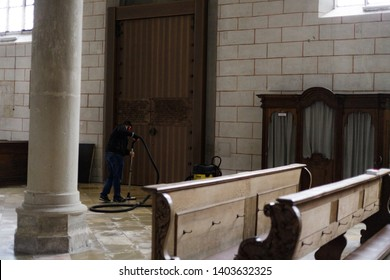 Augsburg, Germany - April 12, 2019: Janitor cleaning the marble floor of the Augsburger Dom (Translate: Cathedral of Augsburg)