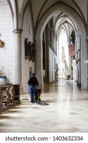 Augsburg, Germany - April 12, 2019: Janitor cleaning the marble church floor of the Augsburger Dom (Translation: Cathedral of Augsburg)