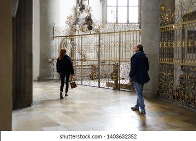 Augsburg, Germany - April 12, 2019: Man and woman exploring the inside and the side chapels of the Augsburger Dom (Translation: Cathedral of Augsburg)
