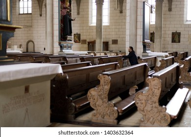 Augsburg, Germany - April 12, 2019: Man who is sitting on wooden church pew prays in the Augsburger Dom (Translation: Cathedral of Augsburg)