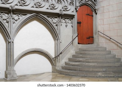 Augsburg, Germany - April 12, 2019: Red door at the top of stone stairs inside of the Augsburger Dom (Translation: Cathedral of Augsburg)