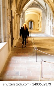 Augsburg, Germany - April 12, 2019: Woman walking through a side corridor of the Augsburger Dom (Translation: Cathedral of Augsburg)