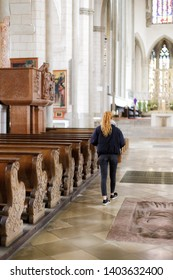Augsburg, Germany - April 12, 2019: Woman walking along church pews down the aisle of the Augsburger Dom (Translation: Cathedral of Augsburg)