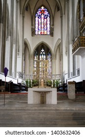 Augsburg, Germany - April 12, 2019: Altar and crucifix in front of stained-glass church windows in the Augsburger Dom (Translation: Cathedral of Augsburg)