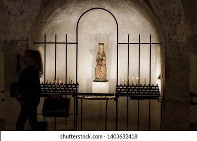 Augsburg, Germany - April 12, 2019: Woman walking away from the sculpture of Virgin Mary in a room underneath the Augsburger Dom (Translation: Cathedral of Augsburg)