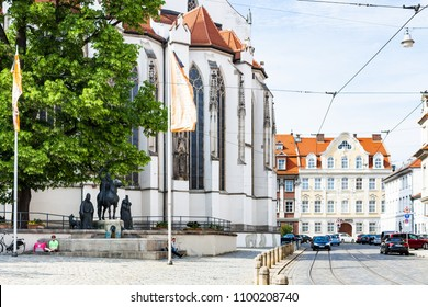 AUGSBURG, GERMANY - MAY 20, 2018: people near fountain with statues of St Afra, Bishops Simpert and Ulrich near Cathedral. Augsburg is a city in Swabia, Bavaria, it is third oldest city in Germany