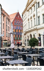 AUGSBURG, GERMANY - MAY 20, 2018: empty outdoor cafe and people on street Philippine-Welser-Strasse in Augsburg town in rain. Augsburg is a city in Swabia, Bavaria, it is third oldest city in Germany