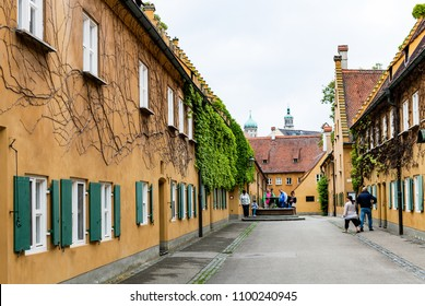 AUGSBURG, GERMANY - MAY 20, 2018: visitors near well in Fuggerei housing in Augsburg town. Augsburg is a city in Swabia, Bavaria, it is third oldest city in Germany