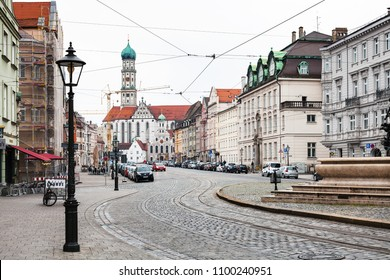 AUGSBURG, GERMANY - MAY 20, 2018: people on Maximilianstrasse and view of Basilica SS Ulrich and Afra in Augsburg town. Augsburg is a city in Swabia, Bavaria, it is third oldest city in Germany