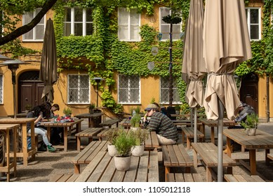 Augsburg,Germany-May 18,2018: Art students sit at a table in the Fuggerei housing complex drawing