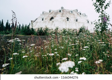 AUGUST 1 2018 - CANTWELL, ALASKA: An abandoned Igloo Hotel, formerly known as Igloo City, sits empty along the George Parks Highway in Alaska. Cow Parsnip wildflowers in foreground