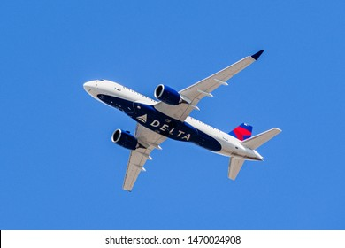 August 1, 2019 Santa Clara / CA / USA - Delta Airlines aircraft in flight; the Delta Logo visible on the airplanes' underbelly; blue sky background
