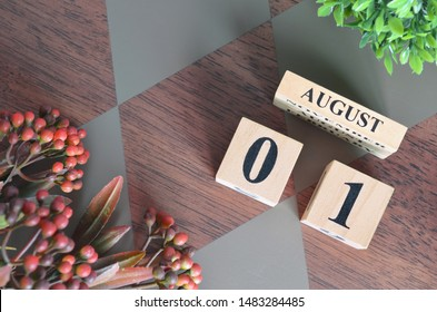 August 1. Date of August month. Number Cube with a flower leaves and bush on Diamond wood table for the background