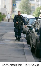 August 11 2008, Helsinki - Finland. Finnish police is responding to bank robbery call at Töölö, Helsinki. Officer inspecting the scene carrying heavy arms.