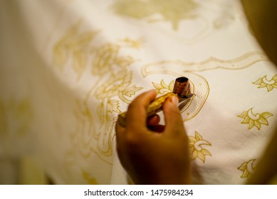 August 11 2019, Surakarta Indonesia : Close Up hand to make batik on the fabric with canting with bokeh background